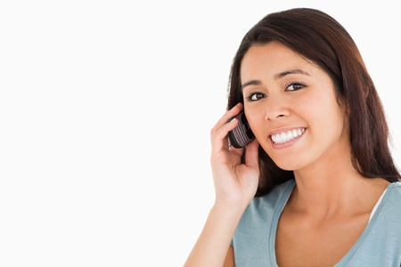 Portrait of a good looking woman on the phone standing against a white background Stock Photo - 11198820