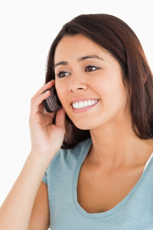 Portrait of a gorgeous woman on the phone standing against a white background photo
