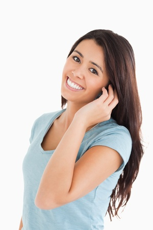 Good looking woman on the phone standing against a white background photo