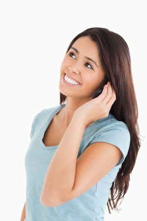 Lovely woman on the phone standing against a white background photo
