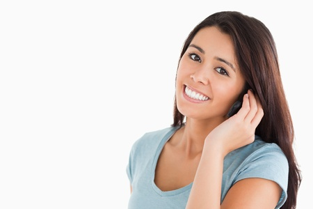 Pretty woman on the phone standing against a white background photo