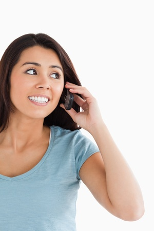 Portrait of an attractive woman on the phone posing against a white background photo