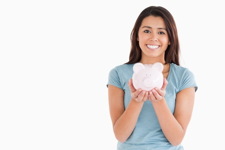 Beautiful woman posing with a piggy bank while standing against a white background photo
