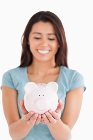 Pretty woman posing with a piggy bank while standing against a white background photo