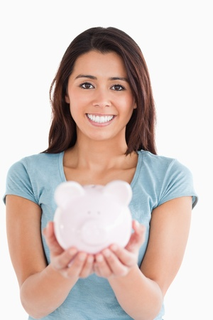Lovely woman posing with a piggy bank while standing against a white background photo