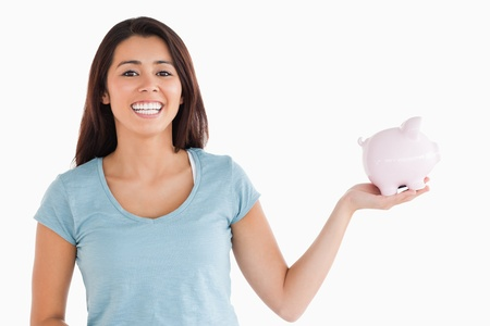 Beautiful female holding a piggy bank while standing against a white background photo