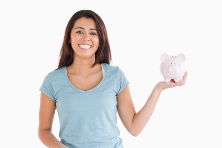Attractive female holding a piggy bank while standing against a white background photo