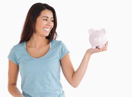 Good looking female holding a piggy bank while standing against a white background photo