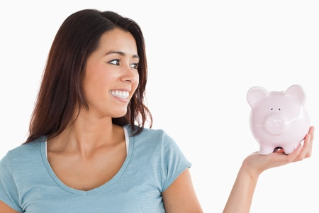 Pretty female holding a piggy bank while standing against a white background photo