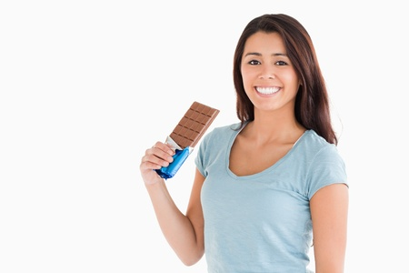 Lovely female holding a chocolate bar while standing against a white background photo