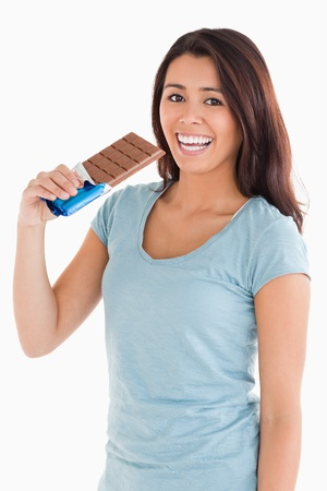 Lovely woman eating a chocolate bar while standing against a white background photo