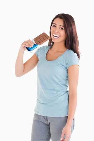 Beautiful woman eating a chocolate bar while standing against a white background photo