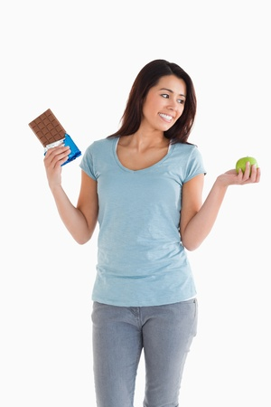 Good looking female holding a chocolate bar and an apple while standing against a white background photo