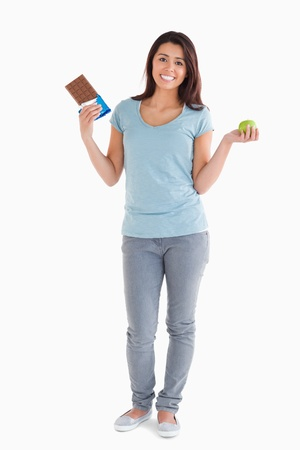 Pretty female holding a chocolate bar and an apple while standing against a white background photo