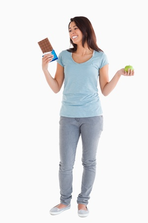 Gorgeous female holding a chocolate bar and an apple while standing against a white background photo