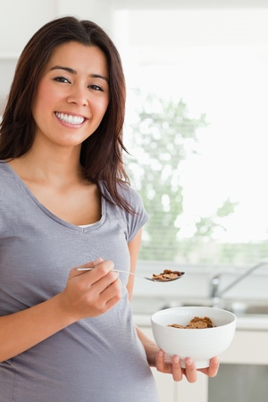 fiber food: Gorgeous pregnant woman enjoying a bowl of cereal while standing in the kitchen