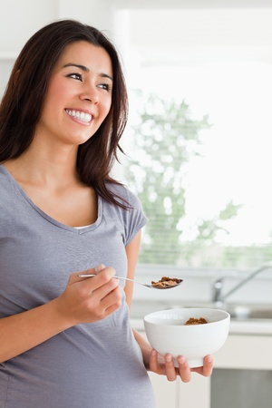 Attractive pregnant woman enjoying a bowl of cereal while standing in the kitchen photo