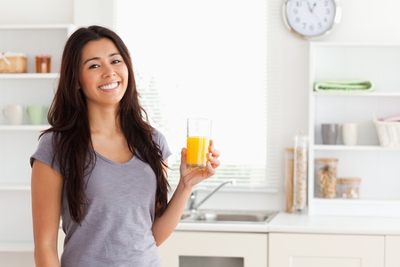Attractive woman holding a glass of orange juice while standing in the kitchen photo