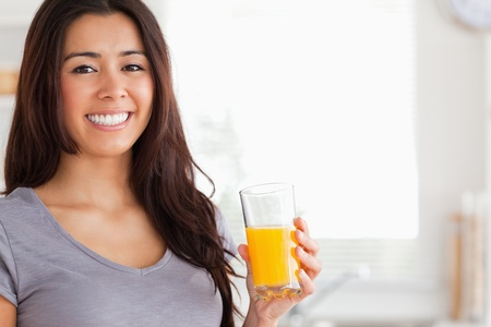 Good looking woman holding a glass of orange juice while standing in the kitchen photo