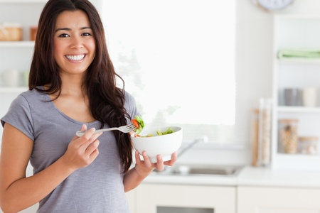 Beautiful woman enjoying a bowl of salad while standing in the kitchen photo