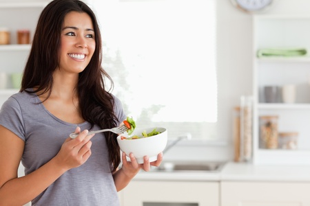 Attractive woman enjoying a bowl of salad while standing in the kitchen Stock Photo - 11204542