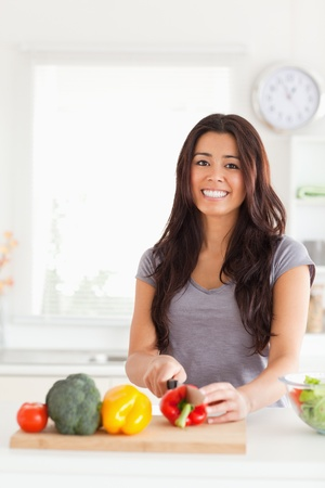 Pretty woman cooking vegetables while standing in the kitchen photo
