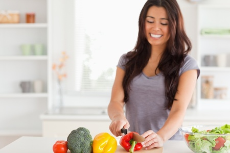 Attractive female cooking vegetables while standing in the kitchen Stock Photo - 11204854