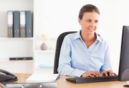 Office worker typing on a keyboard in her office photo