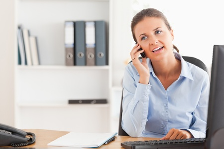 Businesswoman speaking on the phone in her office photo