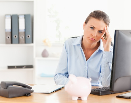 Depressed working woman posing in her office photo