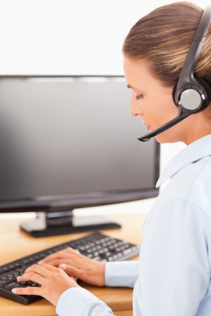 Secretary with a headset working on her computer in her office Stock Photo - 11204085