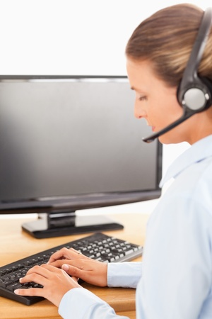 Secretary with a headset working with computer in her office photo