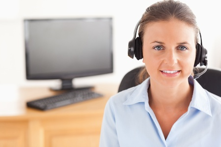 Office worker wearing a headset posing  in her office photo