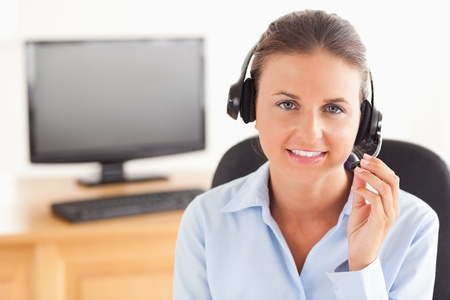 Office worker with a headset posing in her office photo