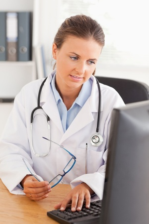 Doctor working on her computer in her office photo