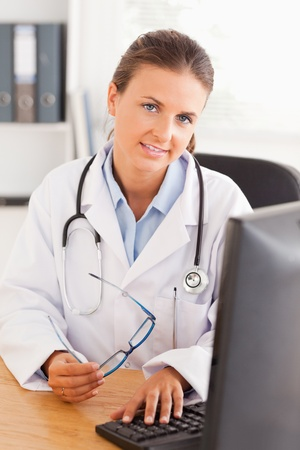 Doctor working with her computer in her office Stock Photo - 11205728