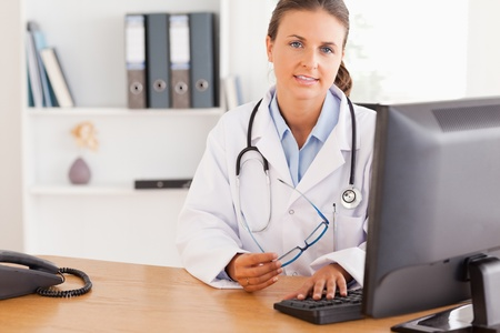 Serious doctor working with a computer in her office Stock Photo - 11205072