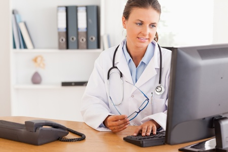 Serious female doctor working with a computer in her office photo