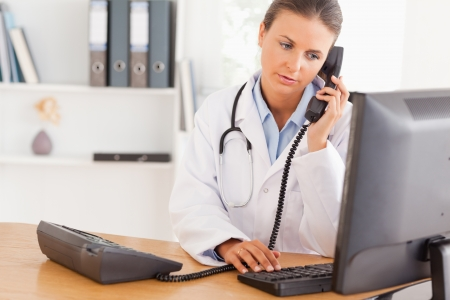 nurse computer: Serious doctor on the phone in her office