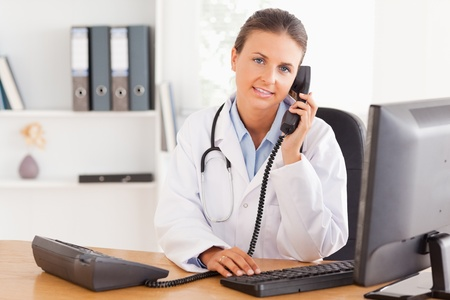 Serious female doctor on the phone in her office photo