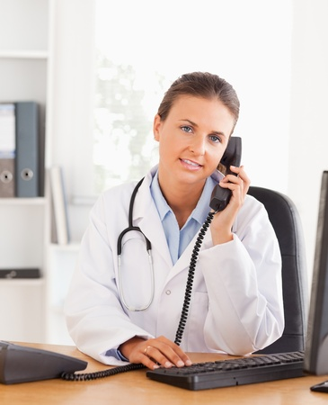 Portrait of a serious female doctor on the phone in her office photo