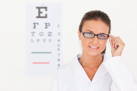 vitamines: Brunette eye specialist wearing glasses looking into the camera in her surgery Stock Photo