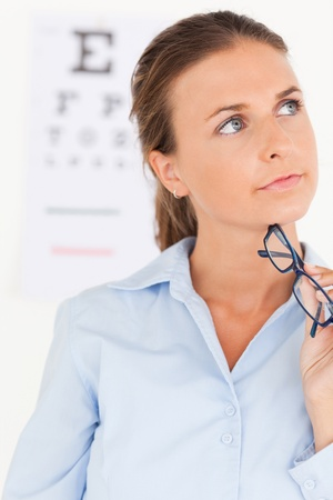 Close up of a eye specialist holding glasses in her surgery Stock Photo - 11204335