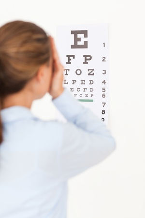vitamines: Woman looking at an eye test in a surgery Stock Photo