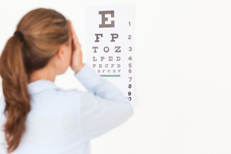 Beautiful brunette woman making an eye test in a surgery photo