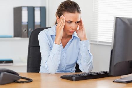 hoofdpijn: Een benadrukt zakenvrouw zit in een kantoor en op zoek naar het scherm
