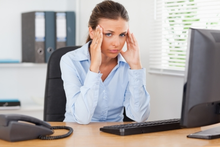 workplace: A stressed businesswoman is sitting at workplace in an office while looking into the camera