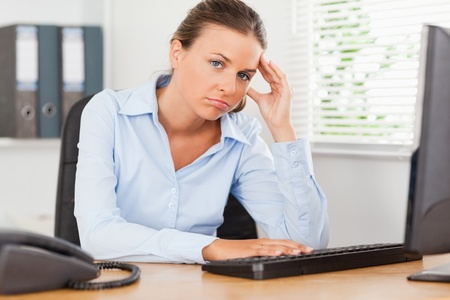 A sad businesswoman is looking into the camera in an office photo