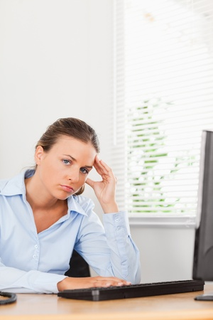 A businesswoman is holding her head in an office photo
