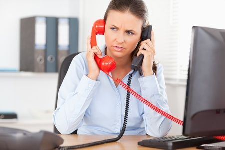 A businesswoman is telephoning with two devices in an office photo